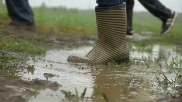 lidé v gumové holínky jsou na zemi. Nohy v holínkách déšť louže. Lidé v holínkách jít přes louži