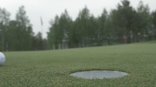 Míč do díry. Golfový míček se pádu do díry. Golf míč do díry na zlaté cestě za jasného slunečného dne