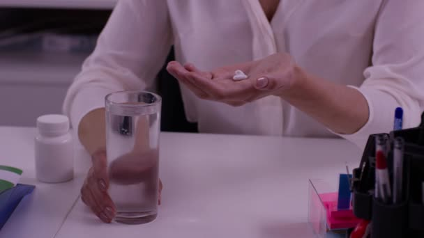 Female hands with glass of water and tablets. Woman hand with pills medicine tablets and glass of water for headache.