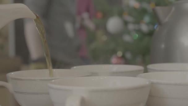 Čaj nalévání do šálku čaje. Rychlovarná konvice nalévá čaj do šálků