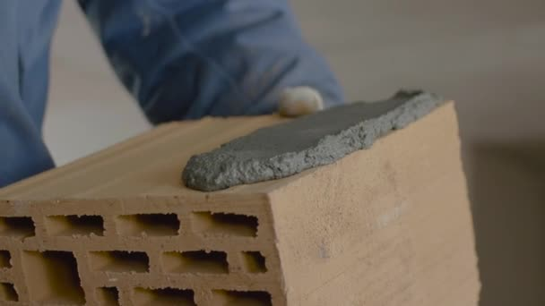 Stavba cihlové zdi. Stěrky, rozprostření cementové na cihly. Pracovní šíří cementu pro cihly