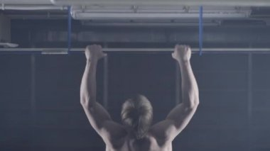Back view of muscular man with naked torso doing pull ups exercise on horizontal bar. Fitness, gymnastics workout in gym. Man with naked torso is pulling on the bar back view