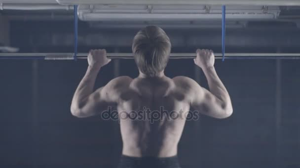 Strong man working out at a gym with bar plate. Pulls up, exercise on the shoulders and arms. Back view. Hold over head. Back view of muscular man doing pull up exercise