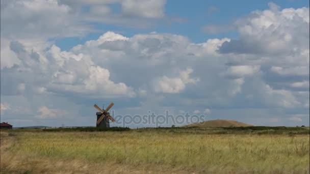 Nyári táj területén a fű, a kék ég és a szélmalom, a távolban. Zöld fű mező táj fantasztikus felhők, a háttérben. Nagy nyári táj. TimeLapse