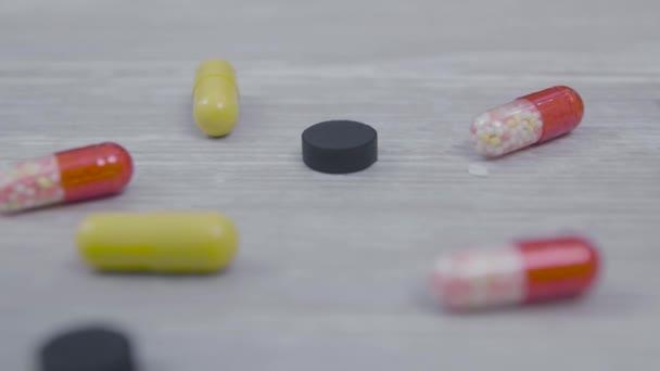 Různé pilulky na dřevěný stůl. Na stole jsou různé prášky