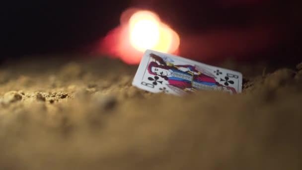 Spiele Karte Jack in den Sand. Filmmaterial. Käfer krabbeln auf Karte ist Jack, Feuer auf den Hintergrund. Abstrakte Spielkarte auf Boden. Alte Spielkarten Jack