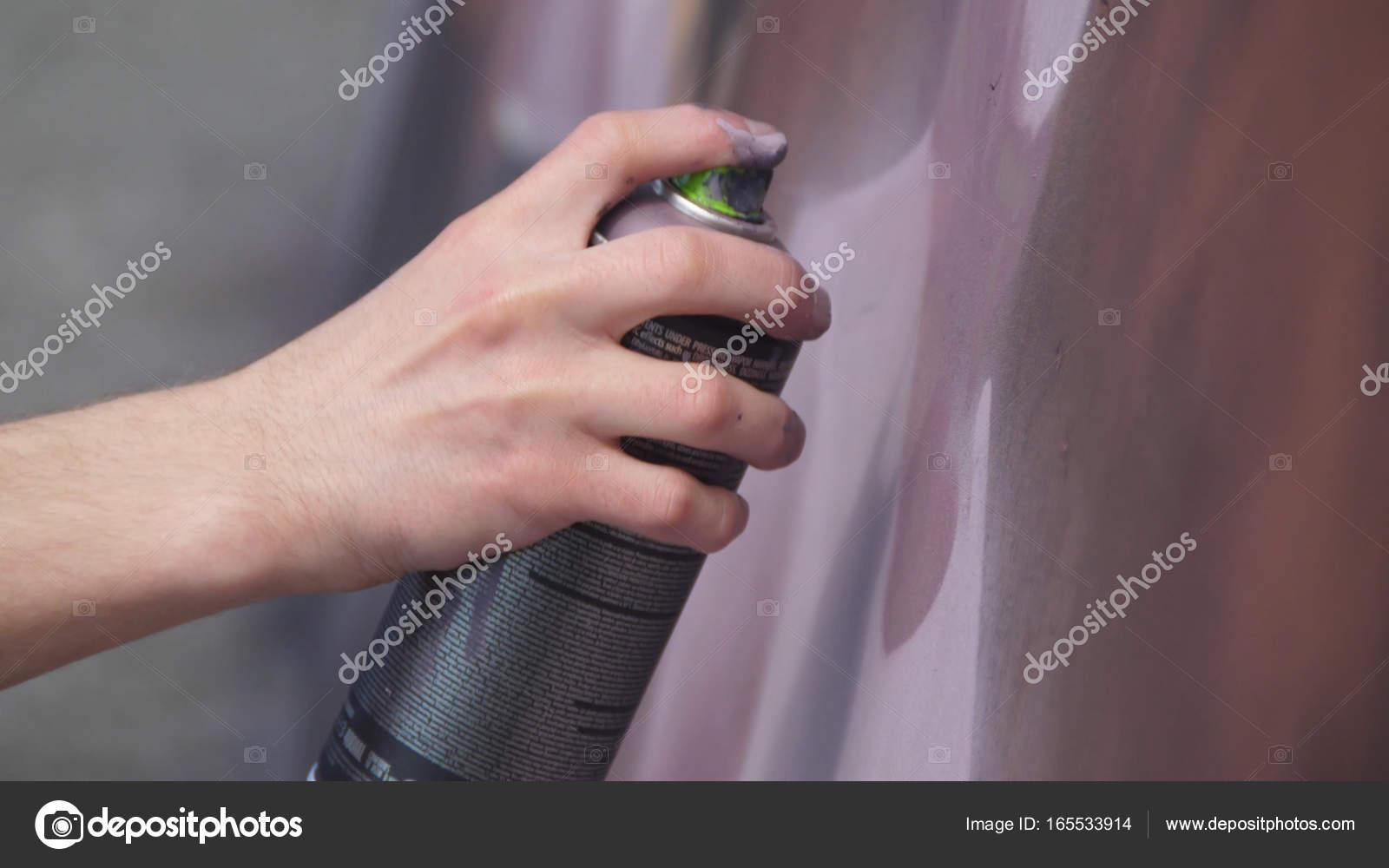 Una mano con un spray puede que dibuja una nueva pintada en la pared ...