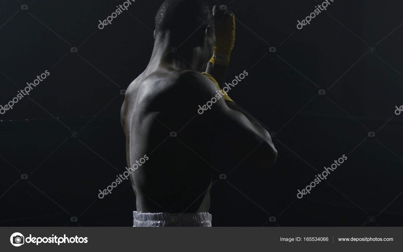 Vista trasera del hombre de boxeo sobre fondo negro. Afro americano ...