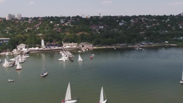 Letecký pohled na plachty lodě plují na moři. Klidné moře a plachty lodí u mola. Jachty a čluny