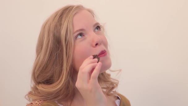 Reiches Mädchen mit Süßigkeiten. Frau essen Schokolade und holen Sie Freude. Mädchen in Tracht essen Schokolade auf weißem Hintergrund