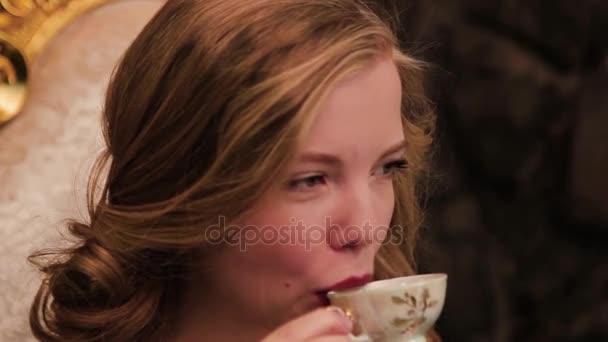 Mladá atraktivní blond žena pití kávy. Krásná žena pít zelený čaj, bílé pozadí. Portrét krásné blond Girl v pití čaje ráno svetr
