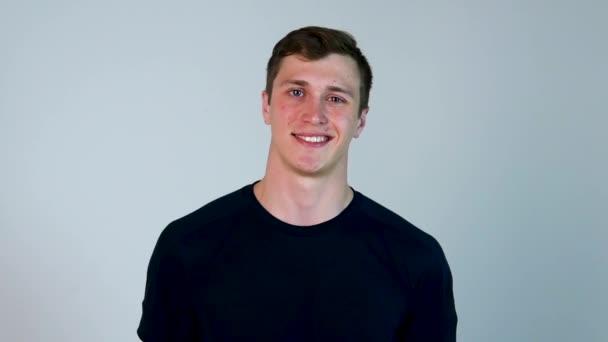 Zdraví a krása koncept - ať se usmívám mladý pohledný muž. usměvavý mladý muž portrét v pomalém pohybu