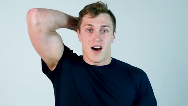 Surprised young man in casual Clothing keeping mouth open and staring at camera while standing against white background. Slow motion