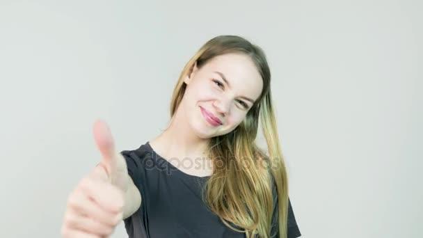 Spokojený úsměv krásná mladá žena ukazuje palec nahoru gesto na bílém pozadí
