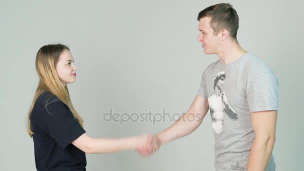 Mladý muž a mladá žena neformální, třes rukou a usmívá se na bílém pozadí