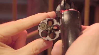 Male hand reload a revolver. Magnum gun without bullets , Magnum revolver and empty bullet, Magnum. lead round nose. 45 auto rim revolver rounds.
