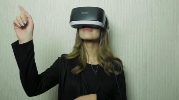 Hezká mladá žena nosí virtuální sluchátka. S úsměvem bokovky pomocí Vr brýle. Bílá grunge zeď s pozadím praskliny. Žena nosí s Vr zařízení a finger Touch ve vzduchu