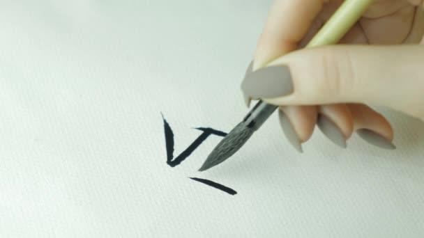 Zenske ruce psaní čínských hieroglyf. Ženské ruky držící stopu psaní kaligrafie čínské znaky, zblízka