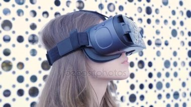 Yyoung attractive woman wearing headset VR virtual reality vision goggles watching video. Young woman with glasses VR, close up