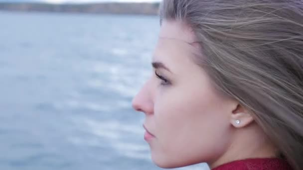Close up of young Woman Relaxing near Lake. Romantic beautiful woman enjoying her time and peaceful nature. Calm and cozy evening