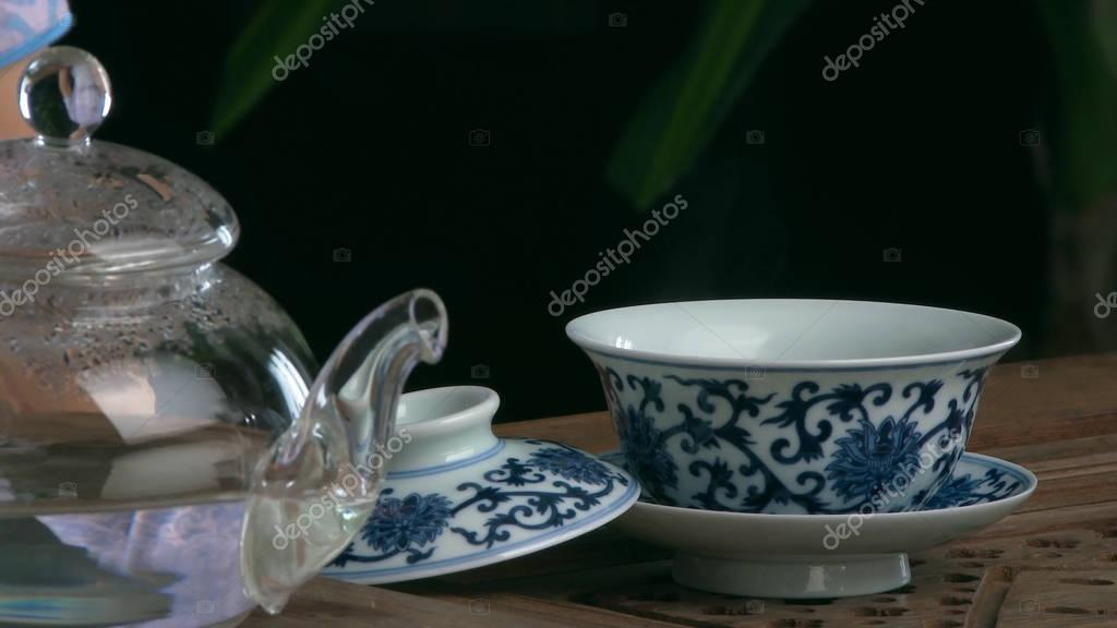 Process brewing tea,tea ceremony,Cup of freshly brewed black tea. Asian tea set on bamboo mat,Closeup. The chinese from a cast teapot