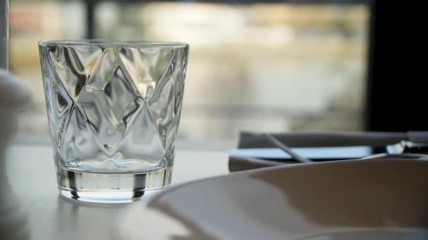Broušené sklenice vody na přírodní pozadí. Čiré broušené sklo s whisky na tmavý dřevěný stůl, detail. Prázdné broušeného skla