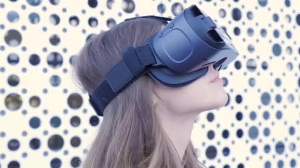 Donna che per mezzo di una cuffia di realtà virtuale su fondo bianco futuristico. Giovane donna attraente che utilizza occhiali Vr-auricolare