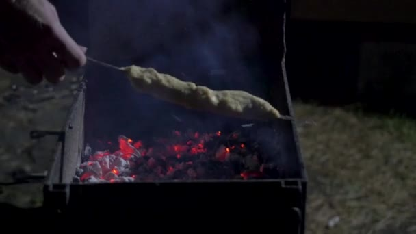 Muž uvedení syrového masa na horkou barbecue gril pomocí dřevěnými kleštěmi, zblízka pohled na tmavém pozadí. Večeře večírek, grilování a pečené vepřové v noci. Gril pozadí