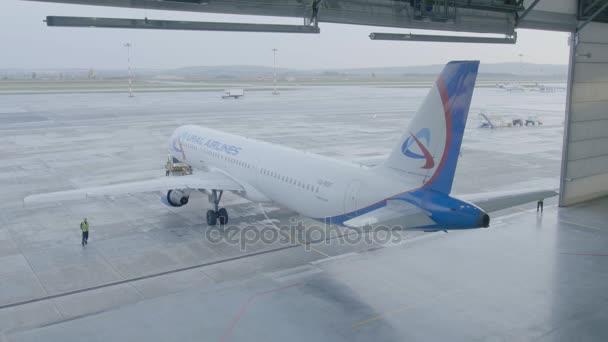 Jekatěrinburg, Rusko - srpen 2017: Letadlo v hangáru, za celé letadlo a uličky. Osobní proudové letadlo bílé barvy. Letadla v hangáru