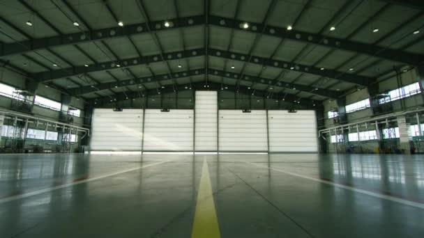 Roll nebo závěrky dveře hangáru letiště. Okenice, dveře či garážová vrata a betonová podlaha uvnitř výrobní haly pro průmysl pozadí. vlnité kovové dveře Komerční budovy