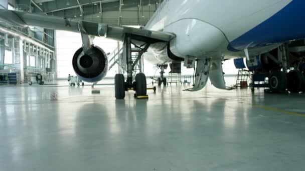 Letadla v hangáru, zadní pohled letadel a světlo z oken. Obchodní tryskové letadlo je v hangáru. Letadla v hangáru, za celé letadlo a uličky