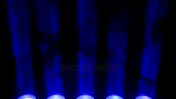 Modrého světla a kouř na černém pozadí. Tmavé pozadí abstraktní s jasně modré etapy reflektory. Světla a kouř. Řadou modrých světel z jeviště.