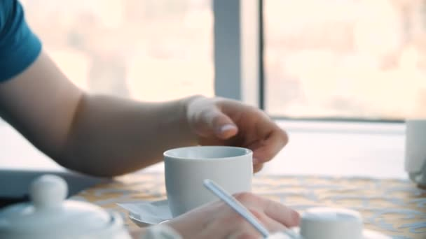 Nahaufnahme einer Hand eines Mannes, der eine Kaffeetasse neben einem Fenster hält. Junger Mann trinkt Kaffee in einem Café vor dem Fenster