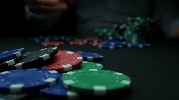 Lancio di fiches da poker su priorità bassa nera delluomo. Poker Chip Multi colore con uno sfondo nero. Primo piano del poker fiches in pile sulla superficie del tavolo verde carta feltro al rallentatore