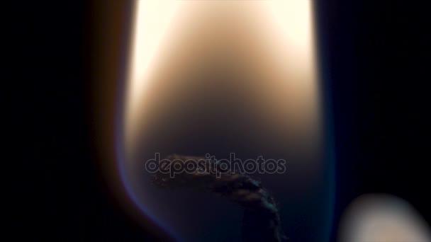 Svíčka plamen zblízka nad černou - Vánoce. Svíčku na černém pozadí closeup. Vesele hoří svíčka makro