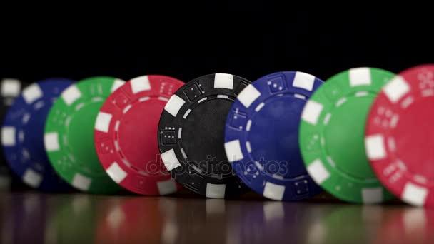 Poker žetony stát v řadě na černém pozadí, dominový efekt. Hrací žetony jsou na stole, symbolem casino