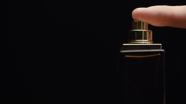 Der Inhalt der Luxusflasche duftet in dunkler Sprühtechnik in Zeitlupe. Parfümflaschenspray auf schwarzem Hintergrund. Sprühen von Köln auf schwarzem Hintergrund. verlieren nach oben von schönen jungen Geschäftsmann mit Parfüm oder