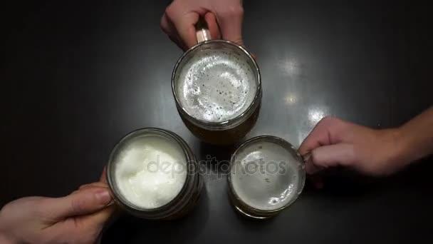 Zdravím. Pohled shora lidí s hrnky s pivem. Shora dolů záběr ze tří půllitr velikosti pivní korbele na stole dřevěný hostinec. Částečný pohled detail mladí přátelé, cinkání, pivní sklenice