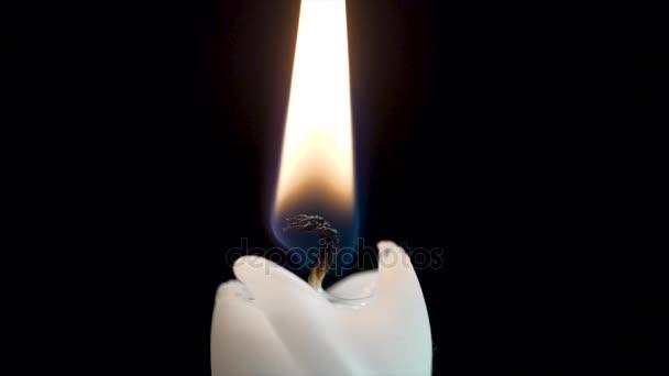 Detail hořící svíčku, plamenem ohně proti černému pozadí. Zblízka svíčka se stezka kouř. Zavřete makro jediná svíčka se