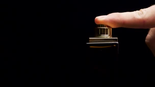 Perfume bottle with male finger on black background. Man applying Perfume. Mans Perfume in the Hand on Black Background. Hand with spray bottle on a dark background