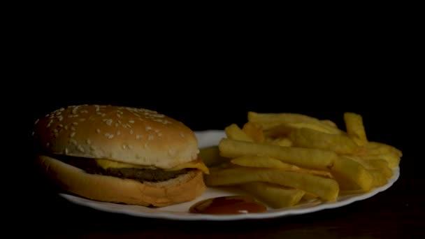 Hamburger s hranolky izolované na černém pozadí. Hranolky na bílé plotně s kečupem a sýrem omáčkou izolované na černém pozadí. Pohled shora. Kuřecí burger deska s hranolky a salátem