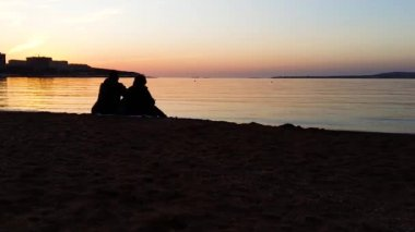 Silhouette of man and woman watching the sunset. Silhouette of the couple enjoying the sunset on the beach. Young couple sitting on a bench at sunset. There is a flying bird, silhouette.