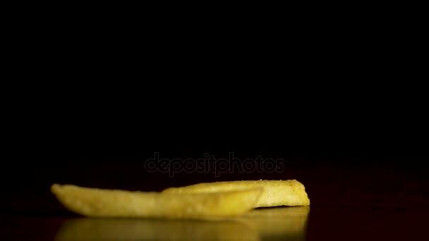 Francouzské hranolky spadají na stole izolované na černém pozadí. Bramborové lupínky spadají na stole izolované na černém pozadí. Létající čipy closeup