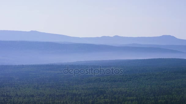 Fenséges panoráma zöld hegyek napsütötte gerendák. Kora reggel köd-hegység. nyári táj. Köd, a tűlevelű erdő veszi körül, a hegy tetején, a naplemente fény