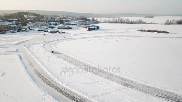 Jedno auto, jízdy po zimním lese na venkovské silnici. Pohled shora z DRONY. Letecký pohled na sněhu v zimě, auto kolem krytý silniční. Pohled shora z auto na zasněžené vozovce
