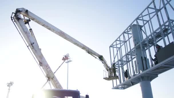 Bauarbeiter auf einer Hebebühne auf einer Baustelle. Männer bei der Arbeit. Bauarbeiter beim Aufbau eines Baugerüstes auf der Baustelle. Männer montieren Werbetafel am Zapfhahn