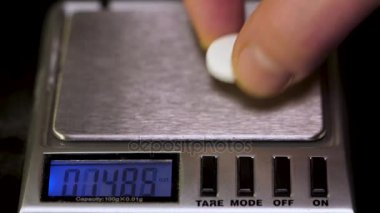 Close up of electronic scales being in use. Laboratory scales. Pills and medication health, close up. Weight Measurement and Analysis Instruments Electronic Analytical Balance.