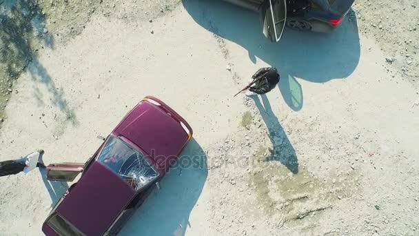Letecký pohled na lupiče s pistolí zastřelil auto a odejít. Záběry. Terorista nebo auto zloděj míří na ovladači. Ozbrojený muž v masce ohrožuje pistole řidiči vozu