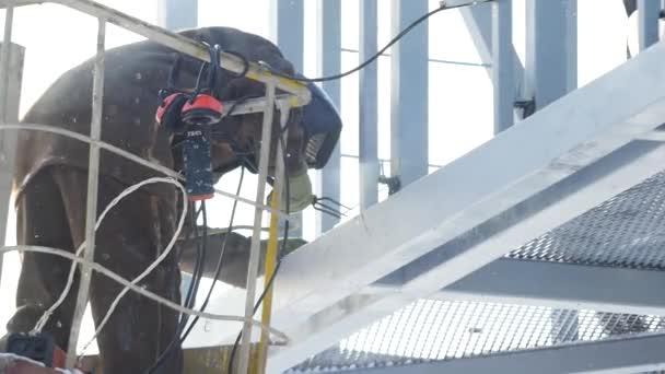 svářeče pracující s elektrodou na obloukové svařování v stavební lokality zima venku. Svářeč ochranné masky práce venku v zimě zblízka