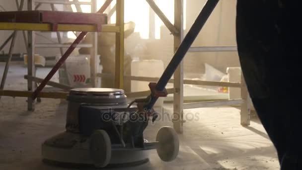 Leštící stroj pro podlahy closeup. Na sanaci rodinných domů, parket, broušení, polishin. Muž leštidla podlahy v místnosti. Opravy bytů v domě, drahé